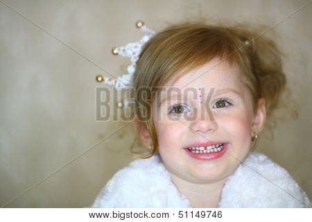 Facial portrait of a little girl with a crown and rhinestones on his head