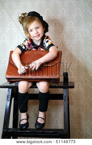 A little girl in black beret with a large portfolio
