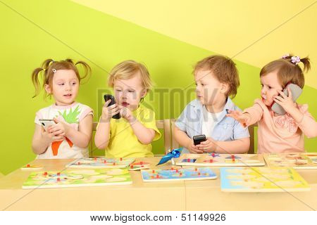Two boys and two girls with phones in their hands are sitting at a table with toys