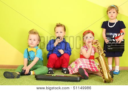 Mods two girls and two boys at the bright green wall with a trumpet and a toy piano