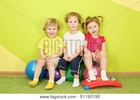 Two boys and a girl with metallophone sitting on a colorful balls in a bright room