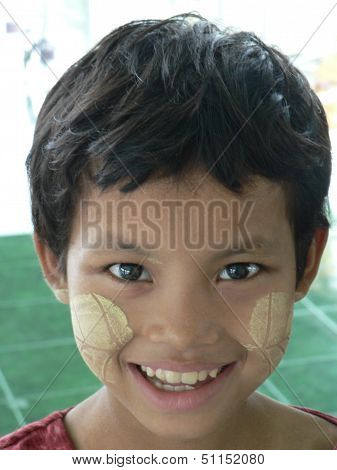 Burmese girl wears traditional thanaka with leaf pattern as sunscreen