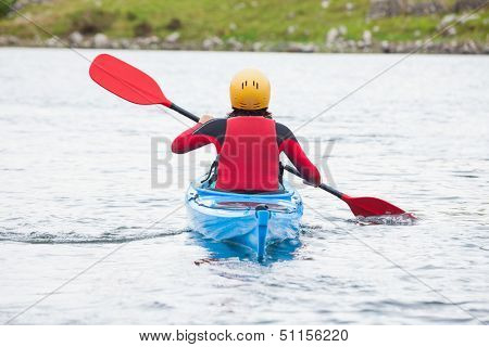 Woman rowing in a kayak in a cold lake