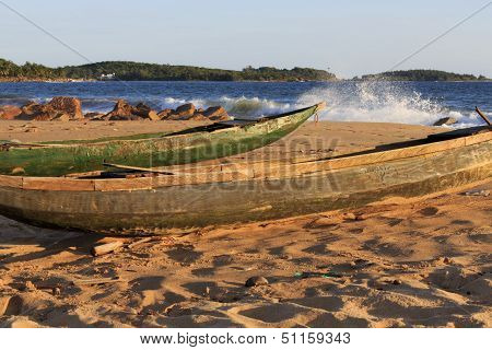 Dugout Fishing Canoe On The Beach With Coast And Spray In The Background