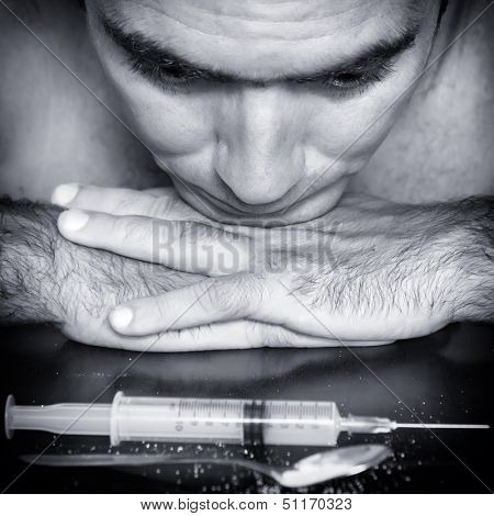 Blue toned portrait of a drug addict contemplating a syringe and drugs with a depressed expression