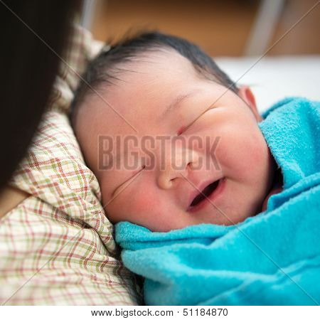 Newborn Asian baby girl smiling and fall asleep in mother's arms, inside hospital room