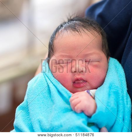 Newborn Asian baby girl smiling and fall asleep in father's arms, inside hospital room