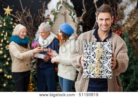 Portrait of handsome young man holding Christmas present with family standing in background at store