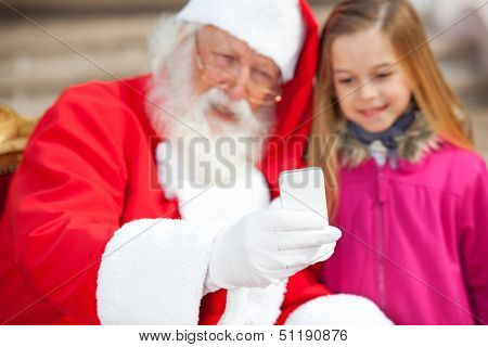 Santa Claus and girl taking selfportrait through smartphone outdoors