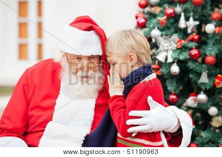 Boy whispering in Santa Claus's ear against Christmas tree