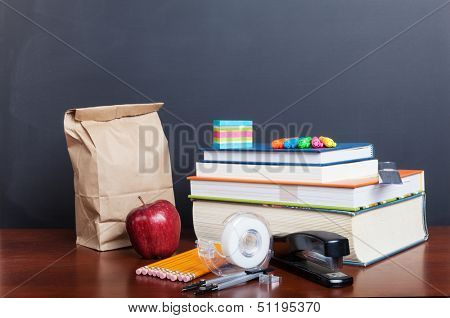 School books with apple and  paper bag lunch on desk in front of a blank chalkboard.