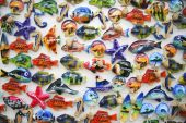 souvenirs on display on boracay beach in the philippines carves in the shape of fish and seashells and painted in bright colors poster