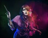 Girl in the image of a witch with a magic wand shot in studio poster