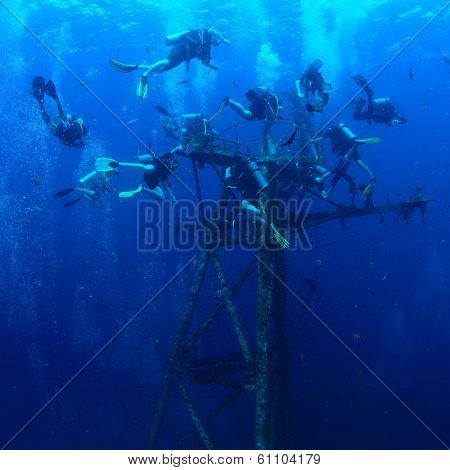 Group of divers exploring ship wreck in the tropical sea