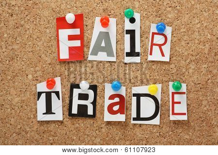 The phrase Fair Trade in cut out magazine letters pinned to a cork notice board poster