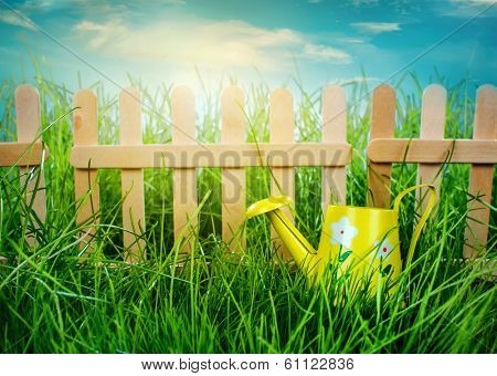 Watering can, Garden grass and wooden fence on blue sky background