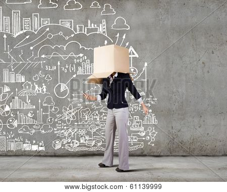 Businesswoman using mobile phone wearing carton box on head