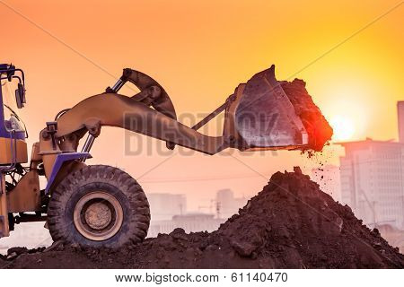heavy wheel excavator machine working at sunset