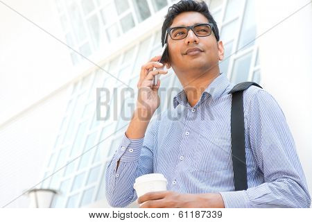 Young Asian Indian businessman on the phone with a cup of coffee in morning, male business man, real modern office building as background.