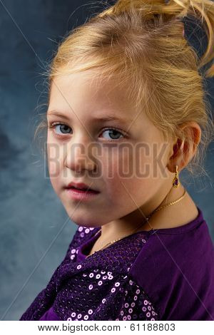 the portrait of a little girl against a gray background.