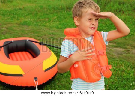 Boy Keeps Watch And Inflatable Boat On Lawn