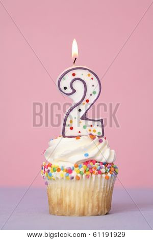 Birthday cupcake with lit candle labeled number 2 on pink and purple background