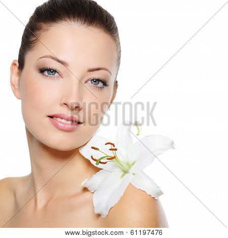 Beautiful clear female face with health skin and white lily on her shoulder poster