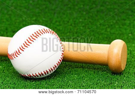 Close-up of wooden bat and baseball ball on artificial green grass