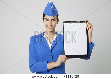 Charming Stewardess Dressed In Blue Uniform with empty blank in hands.