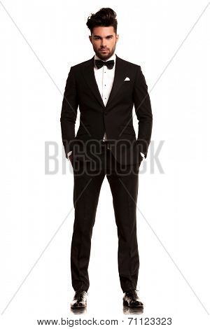 fashion man in tuxedo standing with hands in pockets, full body picture on white background