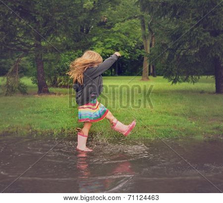 Child Splashing In Dirty Mud Puddle