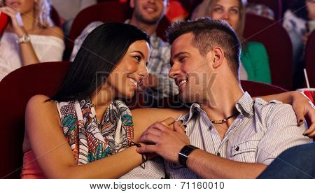Attractive loving couple embracing in movie theater, smiling happy.