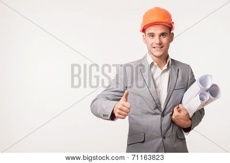 Half-length portrait of young smiling handsome architect engineer in orange helmet posing with blueprints showing thumb up isolated on white background, copyspace poster