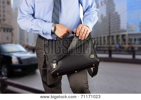 Businessman holding and opening a leather briefcase. City behind poster