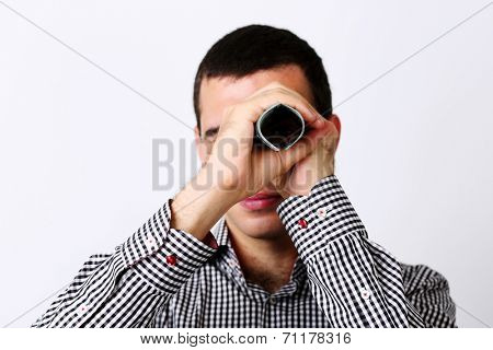 Businessman looks at camera through tube from dollars