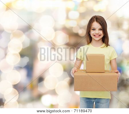 advertising, childhood, delivery, mail and people - smiling little girl holding cardboard boxes over holidays background