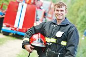 young smiling fireman firefighter in uniform in front of fire engine machine poster