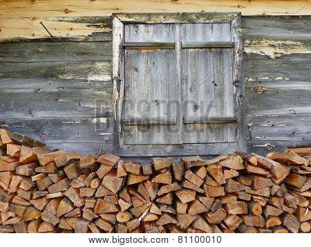 Wooden windows and firewood to the house wall