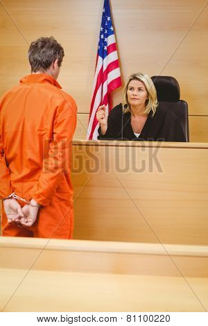 Judge and criminal speaking in front of the american flag in the court room
