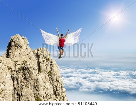 Girl Flies On The Wings Against The Background Of Clouds And Mountain Peaks