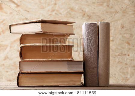 Stack of books on wooden hardboard background