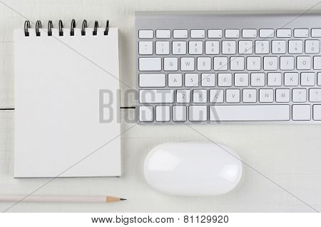 Horizontal image of a white wood home office desk with a computer keyboard, blank note pad, a white pencil, and mouse. A monochromatic still life shot from a high angle.