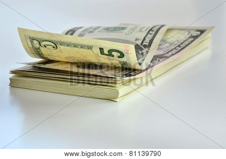 Stack of american dollars on very light background. Focus on first plan.