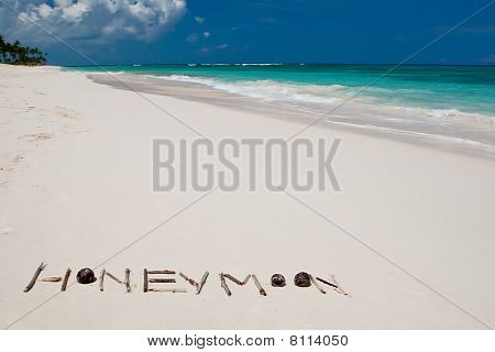 Word Honeymoon On A White Sand Beach Near Blue Ocean