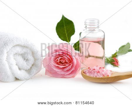 Spa setting with rose ,salt in spoon, oil with towel