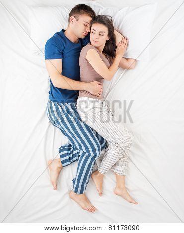 Young couple hugging while sleeping