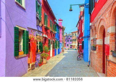 Colorful houses on Burano island, near Venice, Italy. Charming street. Sunny day.
