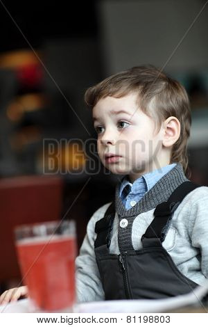 Portrail Of Thinking Child With Red Juice