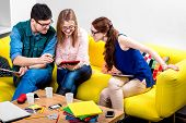 Three young friends or students working with digital gadgets on the yellow couch at home poster
