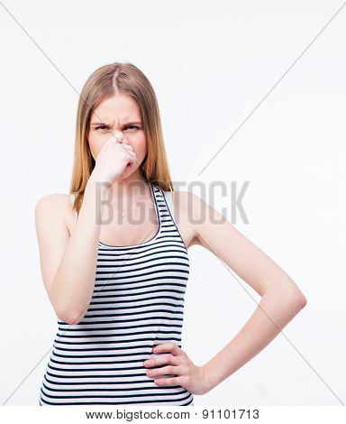Young woman covering her nose with hand over gray background. Looking at camera